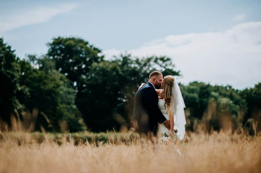 A bride and groom kiss in a corn field in Nottinghamshire