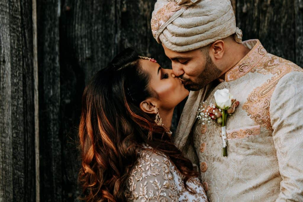 A close up of a newly-wed couple kissing