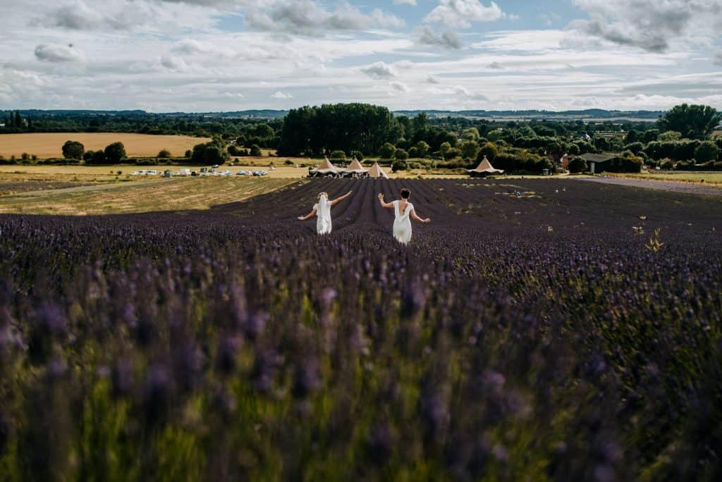 Two brides run through beautiful lavender fields